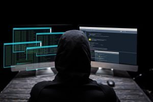 back view of hooded hacker sitting near computer monitors with data on screens on black